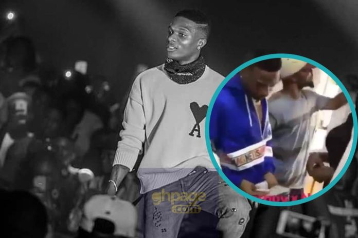 Wizkid gives out dollars to fans at a barbering saloon