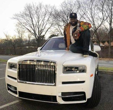 Rapper posing with Rolls Royce