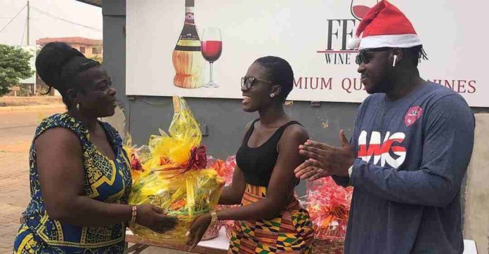 Fella Makafui presenting a gift to a widow on Christmas eve