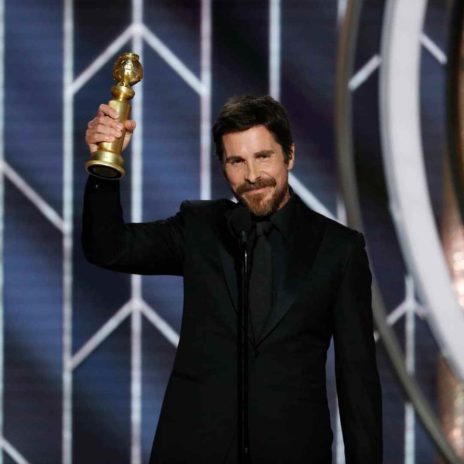 Christian Bale holding his Golden globes award