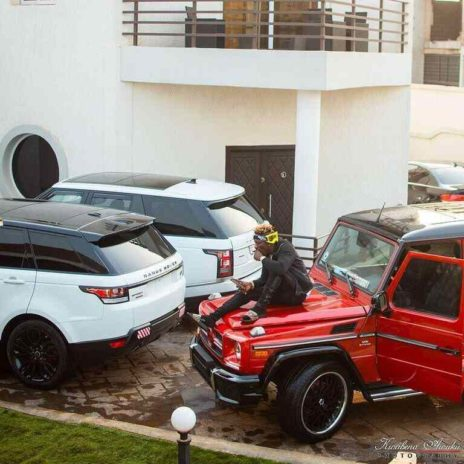 Shatta Wale posing with his cars