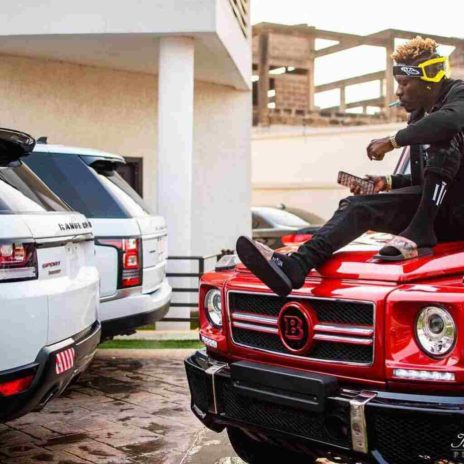Shatta Wale posing with his cars in his house