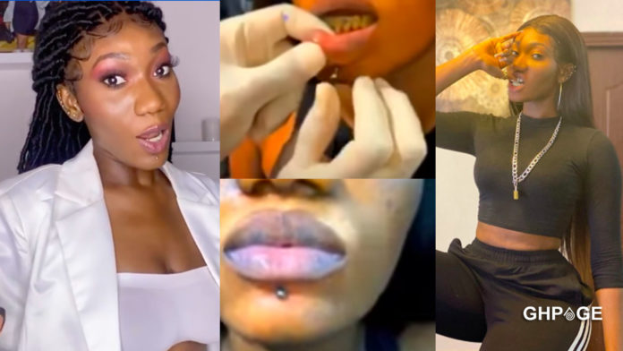 Wendy Shay gets her lips pierced; her scary yellow teeth shows